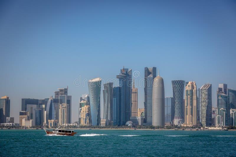 El horizonte de Doha con un barco tradicional en el primero plano en Qatar, en un día del cielo azul, invierno, vista de MIA Park imagen de archivo