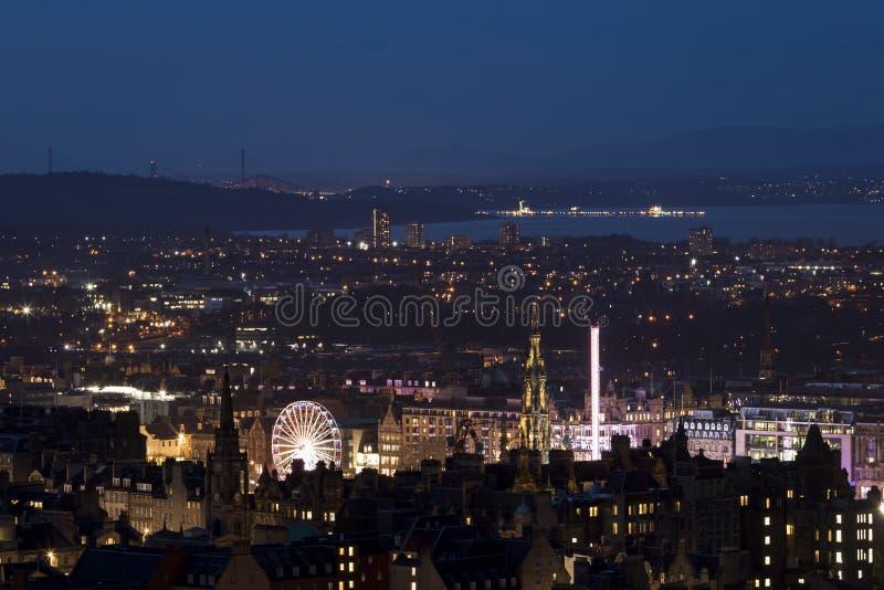 El horizonte de la ciudad de Edimburgo con el mercado de la Navidad se encendió para arriba en la noche imagenes de archivo