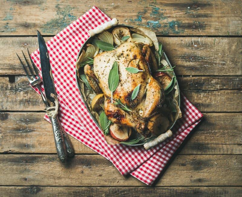 El horno asó el pollo entero en bandeja sobre fondo de madera imagenes de archivo