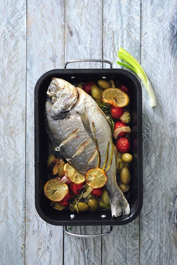 El horno coció pescados de mar enteros con las aceitunas verdes, los tomates de cereza y la mantequilla de hierba fotografía de archivo libre de regalías