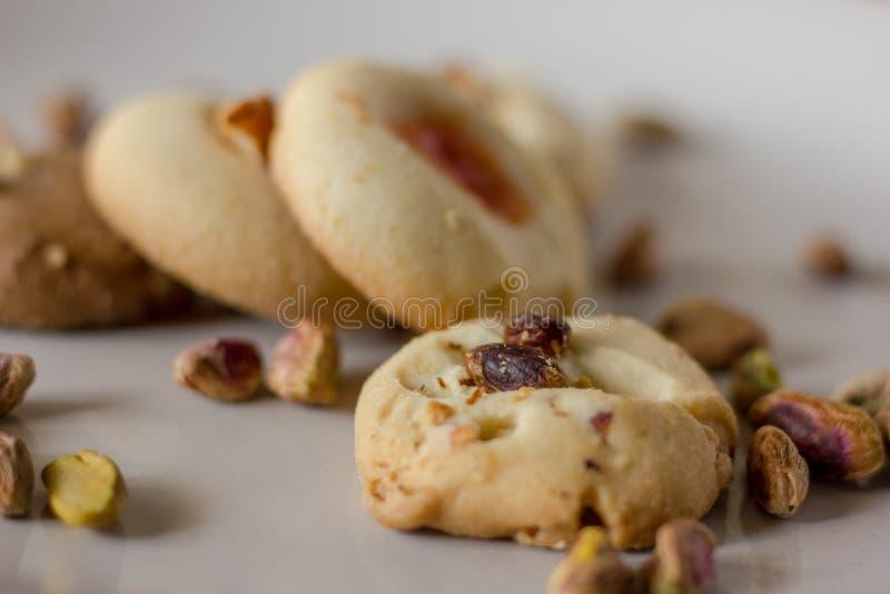 El horno de las galletas de mantequilla del pistacho fresco, con los pistachos asperjados adentro encima de ellos aisló en un fon fotografía de archivo