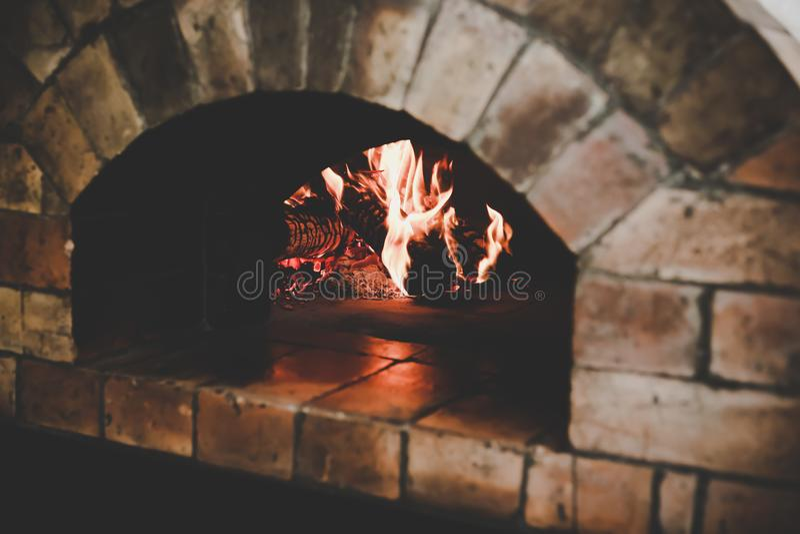 El horno tradicional del vintage hace de ladrillos marrones con la llama y leña para la pizza de cocinar o que cuece o el pan del imágenes de archivo libres de regalías