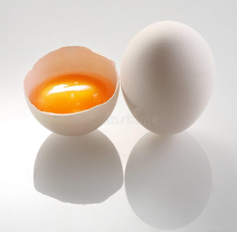 El huevo blanco y una mitad eggs imagen de archivo