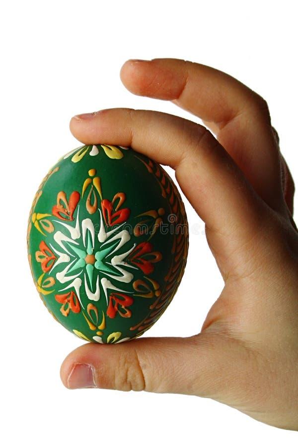 El huevo de Pascua pintado a mano verde se sostuvo en mano derecha del niño joven, fondo blanco imagen de archivo