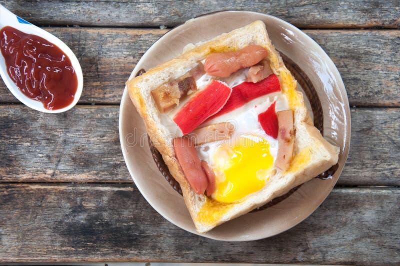 El huevo, el perrito caliente y el cangrejo se pegan en un pan del agujero foto de archivo libre de regalías