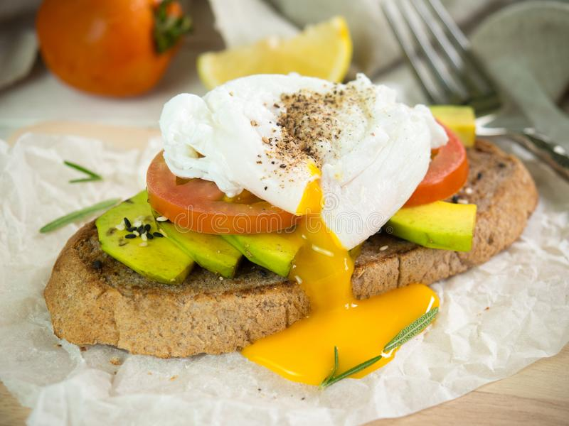 El huevo escalfado, el tomate y el aguacate en el trigo integral tuestan para sano imagenes de archivo