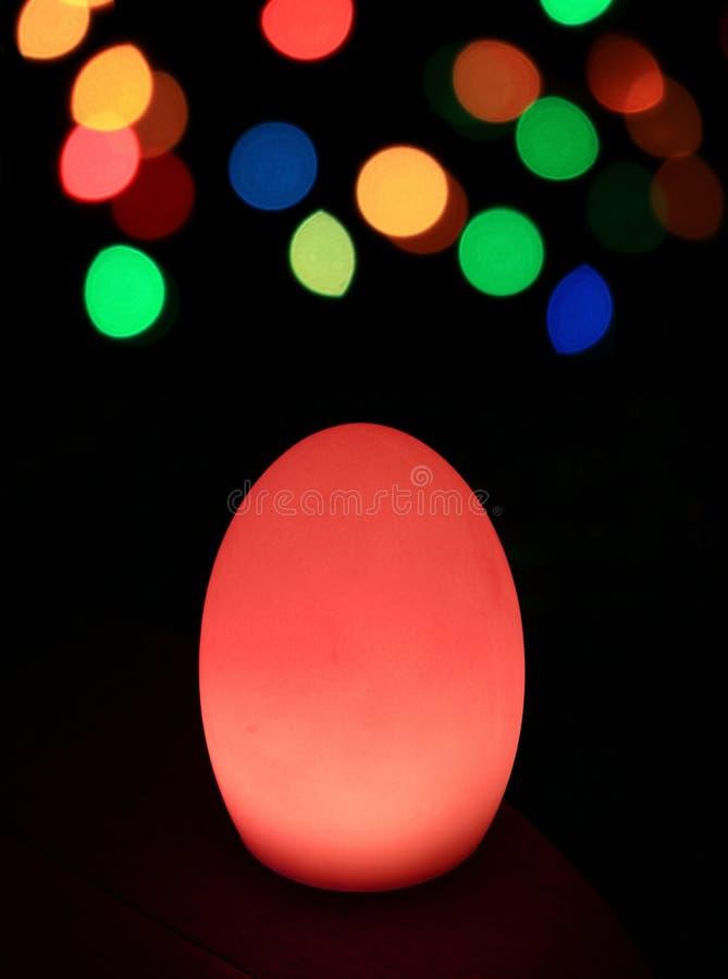 El huevo rojo vibrante formó la iluminación de la tabla con el bokeh colorido en la oscuridad foto de archivo libre de regalías