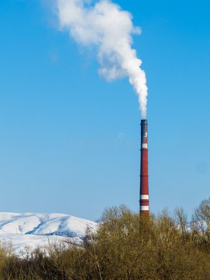 El humo blanco grueso sale del tubo rojo de la fábrica contra un cielo azul claro, montañas nevosas y copas fotos de archivo