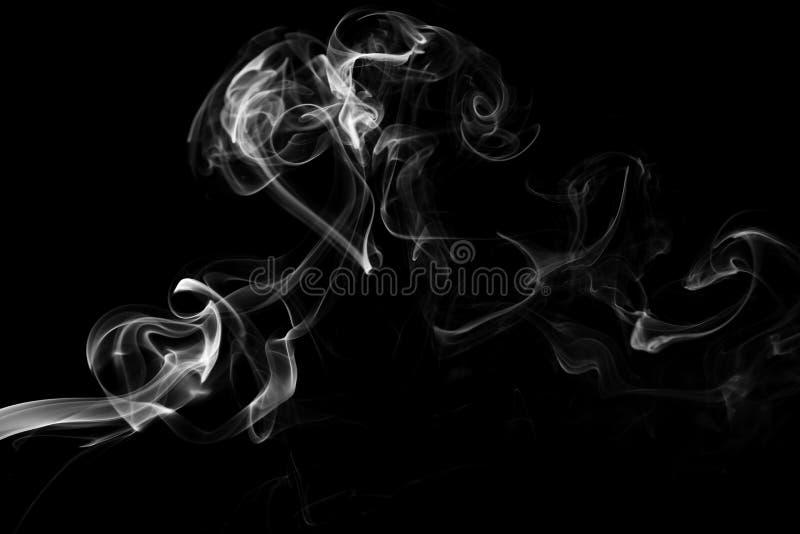 El humo blanco remolina en un fondo negro imagen de archivo