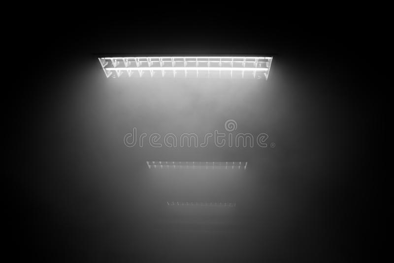 El humo con la luz del tubo de neón fluorescente en un cuarto oscuro fotografía de archivo