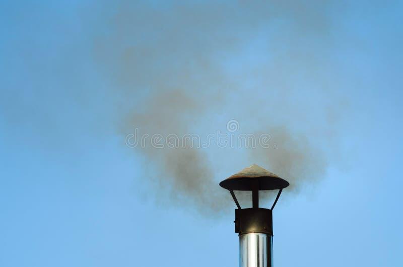 El humo negro viene de un tubo del hierro Sauna del país fotos de archivo