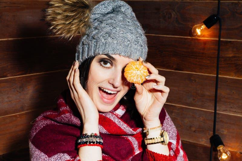 El humor del invierno Mujer de pelo oscuro hermosa joven que sonríe en ropa y casquillo con las mandarinas en fondo de madera fotos de archivo libres de regalías
