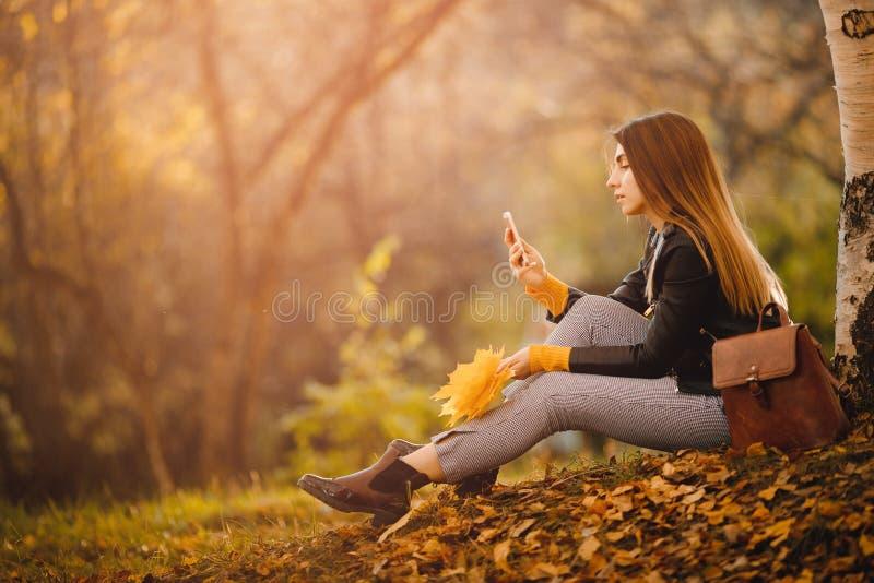 El humor del otoño, muchacha sostiene el teléfono y hace trabajo fotos de archivo libres de regalías