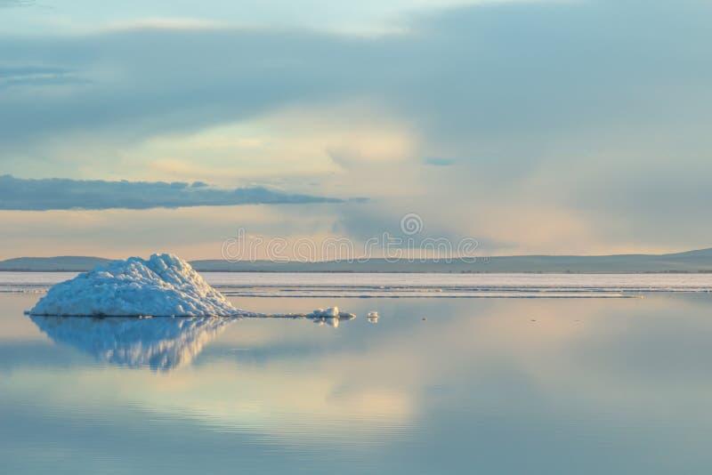 El iceberg de fusión en el lago de la montaña de la primavera en el sol poniente fotografía de archivo libre de regalías