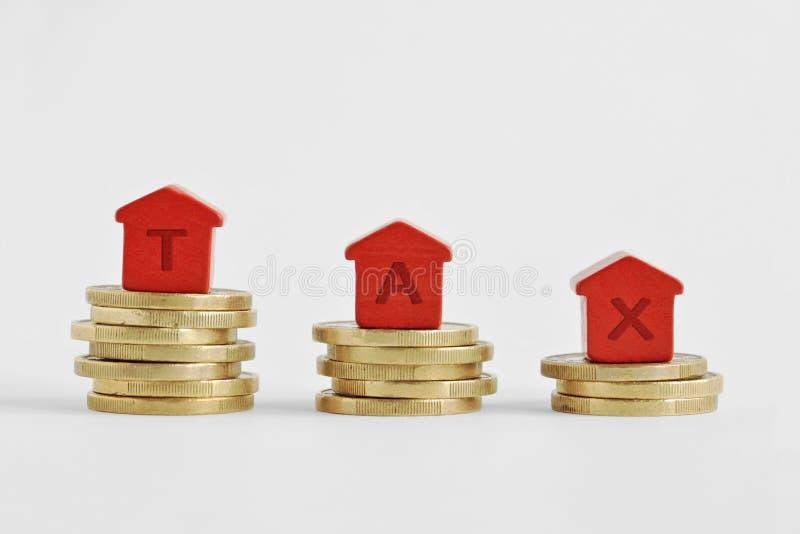 El impuesto escrito con las casas miniatura encima de monedas - Hom de la palabra fotografía de archivo