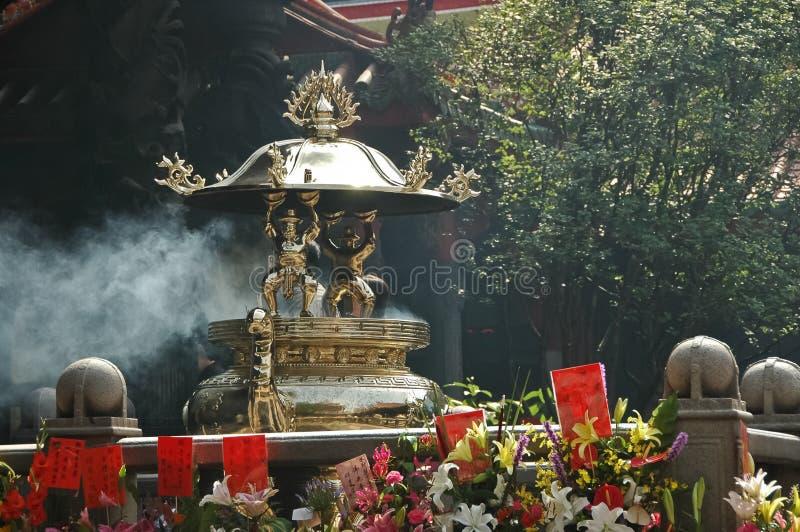 El incienso chino pega la hornilla en un templo viejo foto de archivo