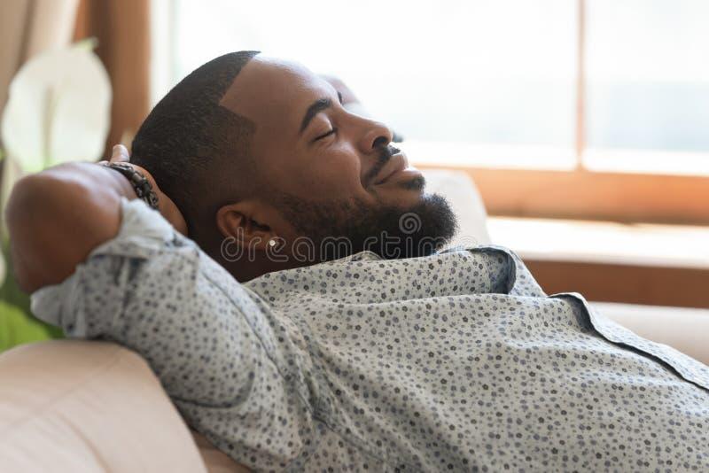 El inclinarse de relajación afroamericano perezoso tranquilo del hombre joven en el sofá fotos de archivo libres de regalías