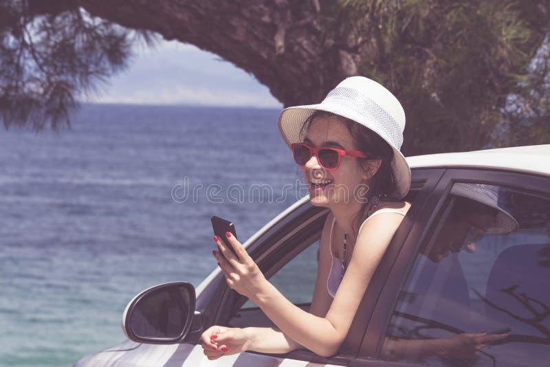 El inclinarse femenino alegre en la ventanilla del coche y usar el teléfono elegante foto de archivo libre de regalías