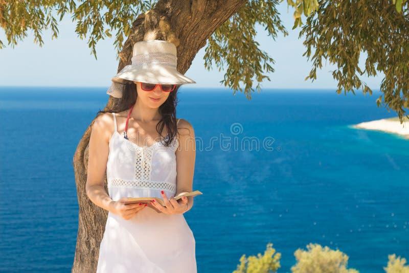 El inclinarse femenino contra el libro del árbol y de lectura fotos de archivo libres de regalías