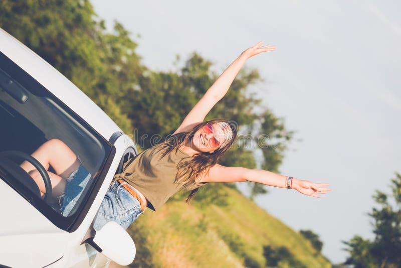El inclinarse femenino de moda fuera de la ventanilla del coche con los brazos para arriba foto de archivo