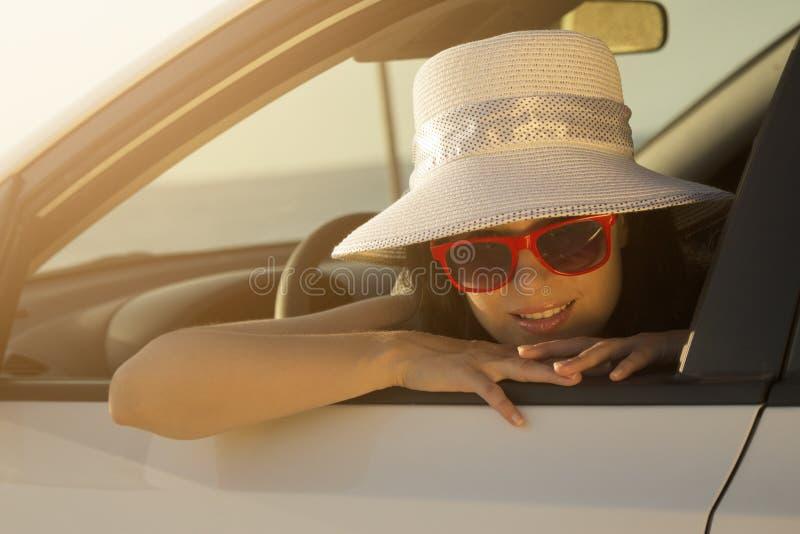 El inclinarse femenino joven en la ventanilla del coche foto de archivo