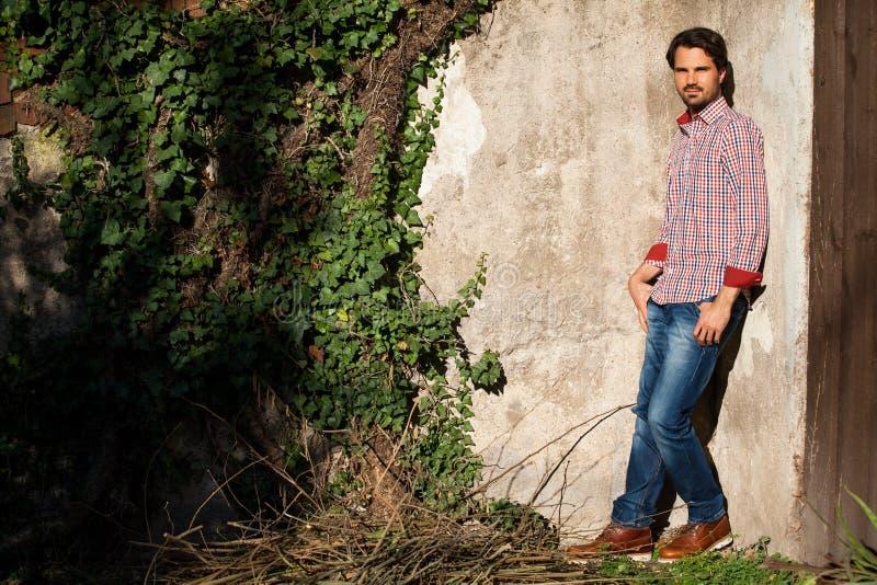 El inclinarse modelo masculino contra la pared fotos de archivo