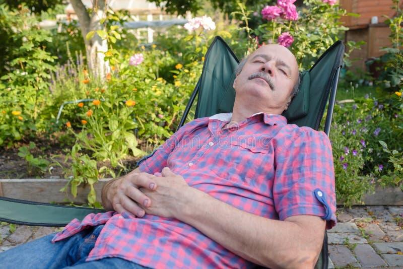 El inclinarse que se sienta del hombre detrás en la silla que duerme en jardín de flores al aire libre del verano fotos de archivo libres de regalías