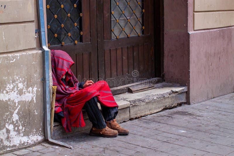 El inclinarse sin hogar contra puerta de granero imagen de archivo