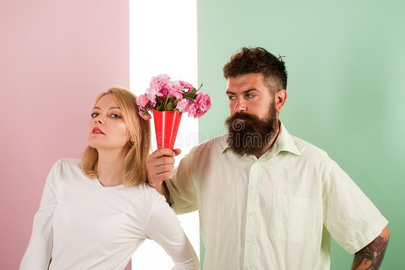 El inconformista barbudo da gesto de la excusa de la muchacha de flores del ramo Hombre con la mujer de los apologyes de la barba foto de archivo libre de regalías