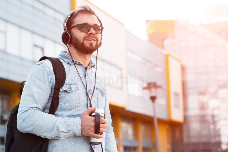 El inconformista berded sonriente con los auriculares escucha la música al aire libre imágenes de archivo libres de regalías