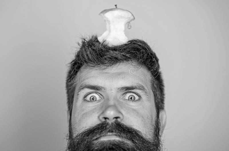 El inconformista chocó la cara con la blanco del tocón de la manzana en el fondo azul principal, cierre para arriba Barba larga d fotos de archivo libres de regalías
