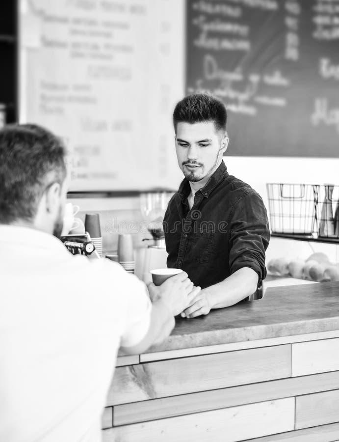 El inconformista elegante hermoso de Barista comunica con el visitante del cliente Café servido a ir El hombre pide bebida en el  fotografía de archivo libre de regalías