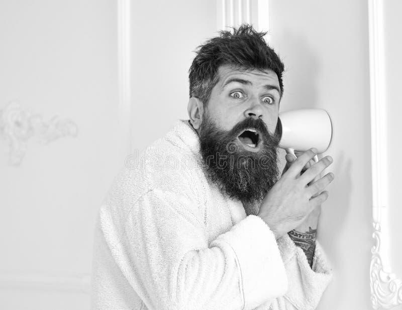 El inconformista en albornoz en cara chocada escucha secretamente conversación Secreto y concepto del espía Hombre con la barba y fotos de archivo