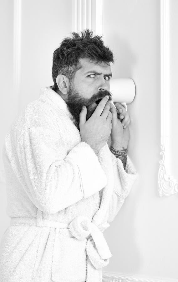 El inconformista en albornoz en cara sospechosa escucha secretamente conversación Secreto y concepto del espía Hombre en el inter imagen de archivo libre de regalías