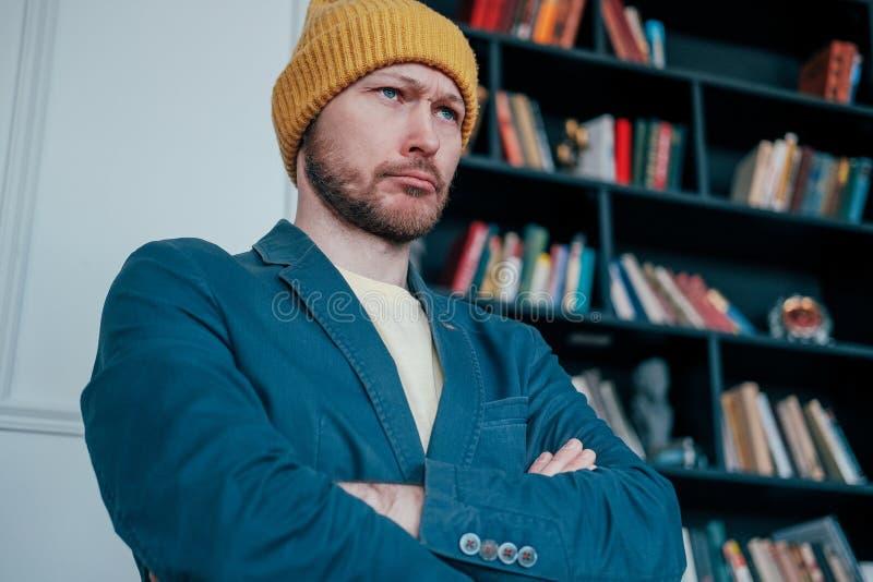 El inconformista enojado barbudo adulto atractivo del hombre en sombrero amarillo mira la cámara y surcó sus frentes en fondo de  foto de archivo