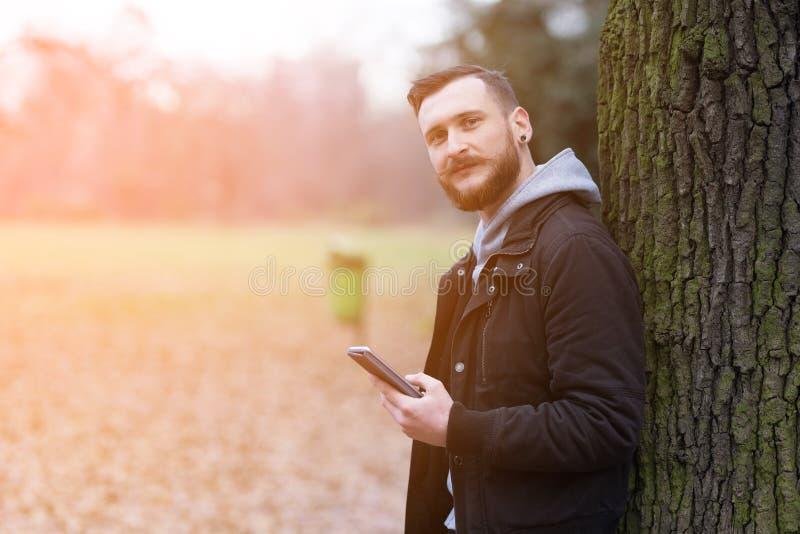 El inconformista sonriente sirve la comprobación de su smartphone en el parque fotografía de archivo