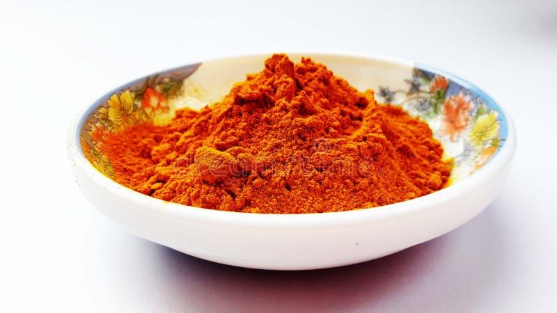 el indio condimenta el chile rojo en el fondo blanco imagen de archivo
