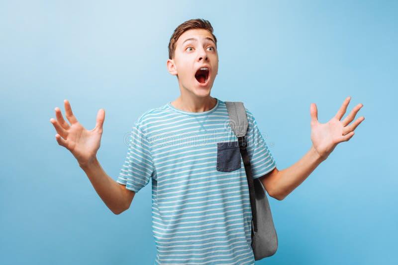 El individuo adolescente emocional presionado aumenta sus manos y clama contra desesperadamente, expresión facial molesta imagen de archivo libre de regalías