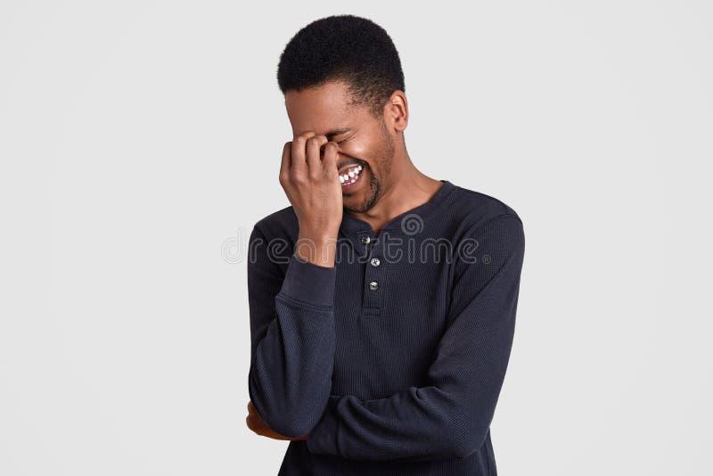 El individuo afroamericano extático ríe feliz algo divertido, estrabismos hace frente, estando alegre, oye broma divertida del am imágenes de archivo libres de regalías