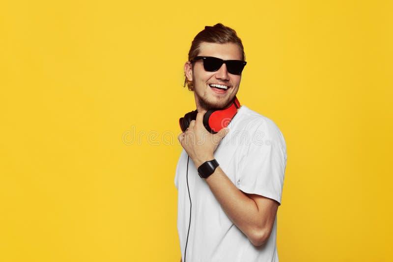 El individuo alegre del inconformista sonríe feliz, ha excitado la camiseta, las gafas de sol y los auriculares blancos que lleva foto de archivo