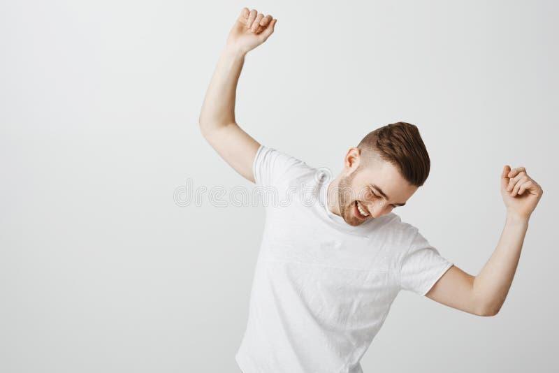 El individuo apuesto feliz y contento con la barba en la camiseta blanca que celebraba con alegría logró el baile del trabajo y imagenes de archivo