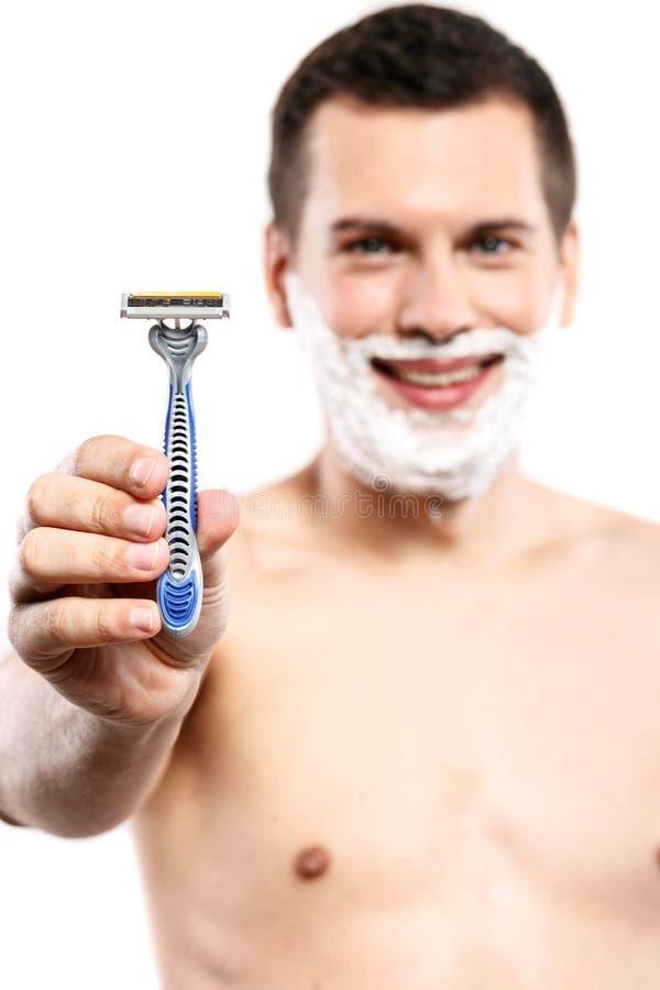 El individuo atractivo está presentando la herramienta para afeitar imagen de archivo libre de regalías