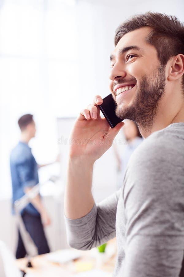 El individuo atractivo está utilizando el teléfono para la comunicación imagen de archivo