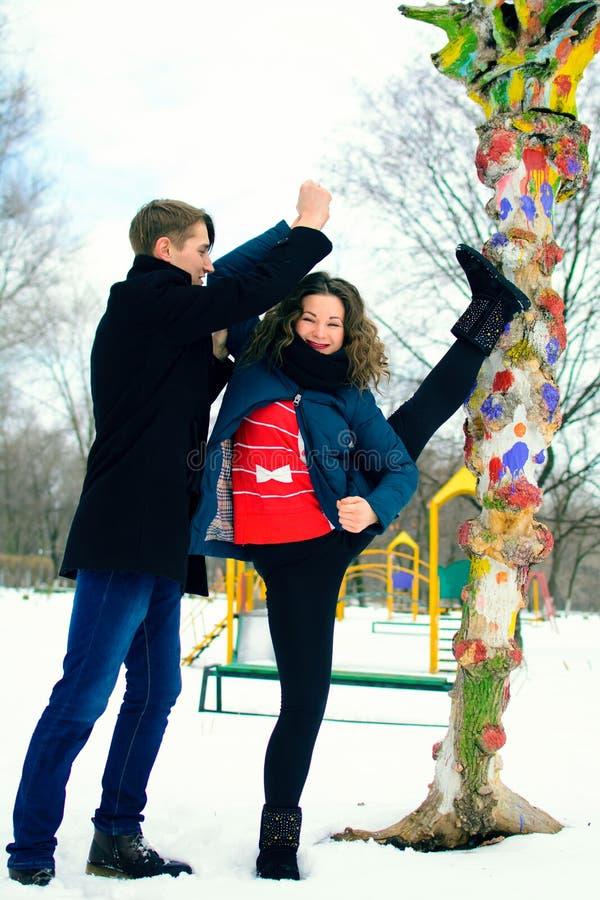 El individuo ayuda a una muchacha a hacer estirar cerca de un árbol en la calle imagen de archivo libre de regalías
