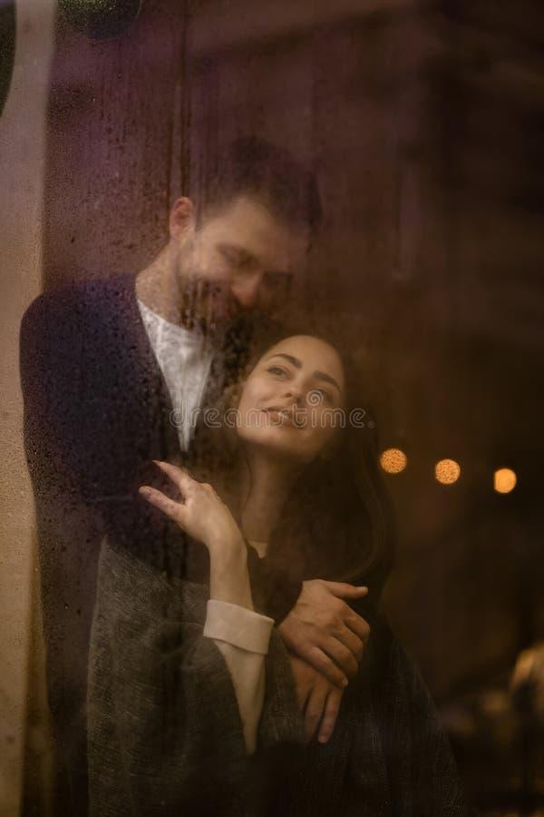 El individuo cariñoso romántico abraza su situación feliz de la novia detrás de una ventana mojada con las luces imágenes de archivo libres de regalías