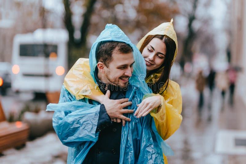 El individuo cari?oso de los pares felices y su la novia vestidos en impermeables est?n abrazando en la calle bajo la lluvia fotos de archivo