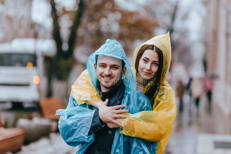 El individuo cari?oso de los pares felices y su la novia vestidos en impermeables est?n abrazando en la calle bajo la lluvia fotografía de archivo