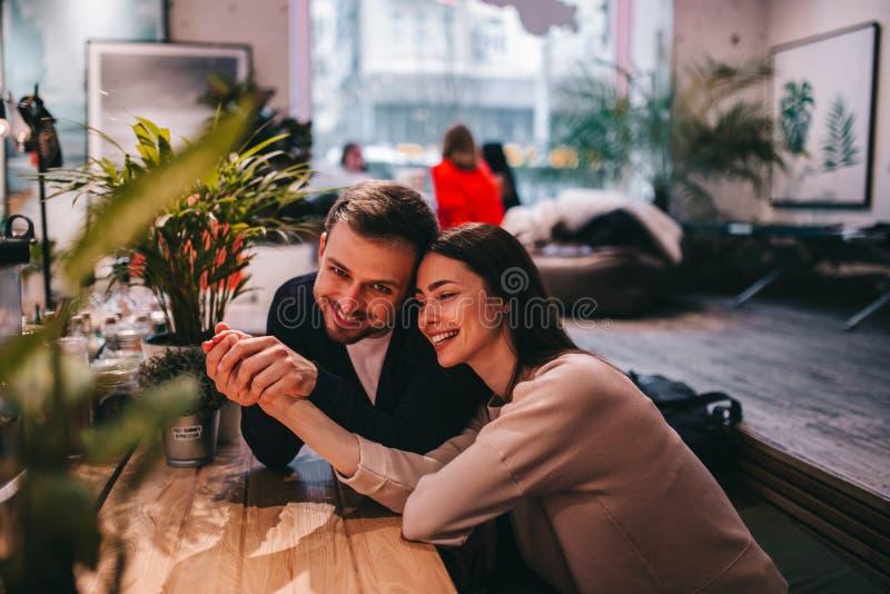 El individuo cari?oso feliz lleva a cabo la mano de su novia que se sienta en la tabla en el caf? y la mira foto de archivo