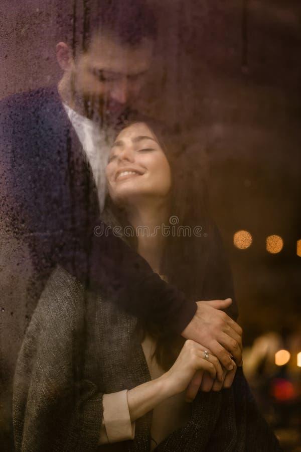 El individuo cari?oso rom?ntico abraza su situaci?n feliz de la novia detr?s de una ventana mojada con las luces foto de archivo libre de regalías