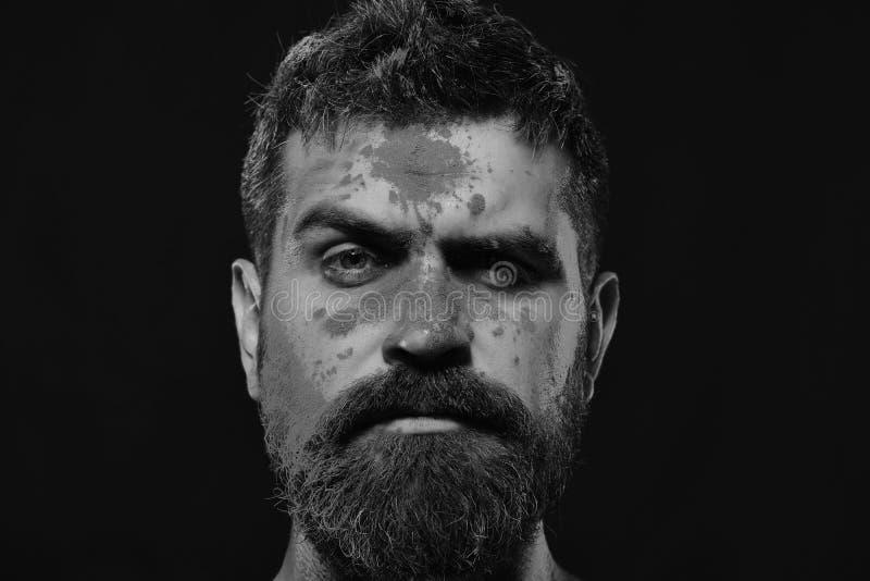 El individuo con la cara dudosa se coloca en fondo negro El hombre barbudo celebra el holi, espacio de la copia Celebración y día foto de archivo